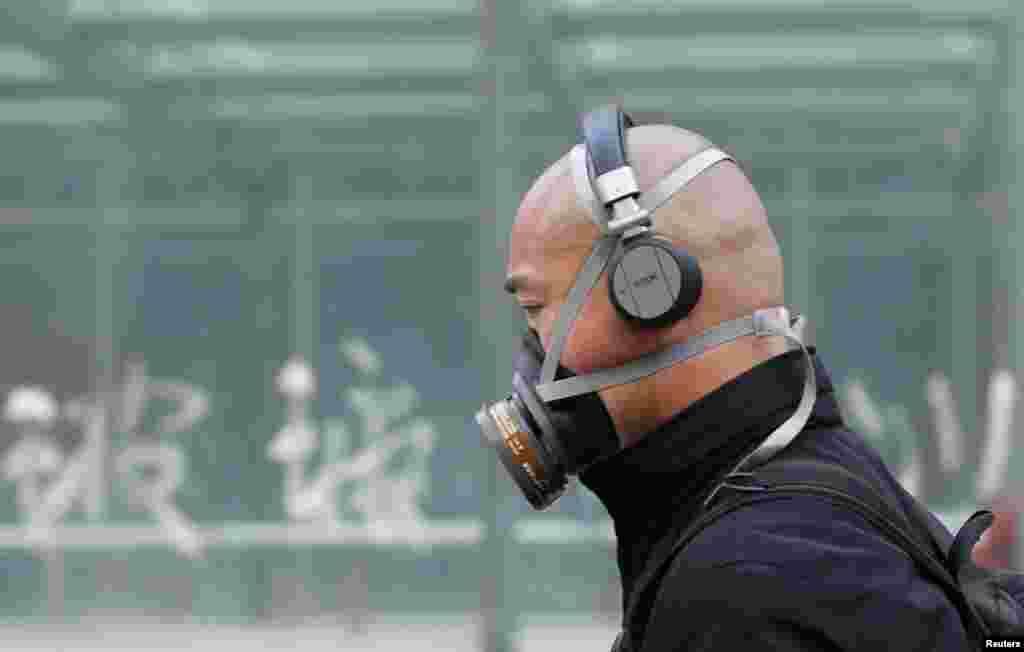 2013年5月2日在北京的街道上,一個人戴了防毒面具。冬季覆蓋了許多北方城市的空氣污染引起的民憤,蔓延到網上,人們也呼籲北京淨化生活用水。