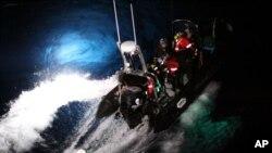 2014年2月23日在南极海,海洋守护者协会的一个橡皮艇上的活动人士试图用绳子套住一只日本捕鲸船