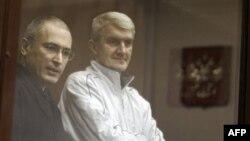 Hai bị can Khodordovsky (trái) và Lebedev bác bỏ những lời buộc tội, và nói rằng họ bị mưu hại vì ủng hộ các ứng cử viên đối lập, và những người chỉ trích ông Putin