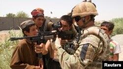 Seorang tentara Inggris menunjukkan senjatanya kepada anak-anak Afghanistan di kota Lashkar Gah, provinsi Helmand (foto: dok). Seorang marinir Inggris dinyatakan bersalah atas pembunuhan warga Afghanistan.