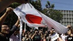 Demonstran Tiongkok membakar bendera Jepang dalam aksi protes anti Jepang di depan Kedutaan Jepang di Beijing (15/9).