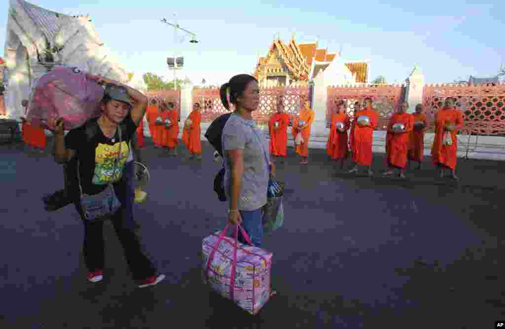 Anti-government demonstrators leave a demonstration site with their belongings, walking past Buddhist monks a day after military soldiers staged a coup, in Bangkok, May 23, 2014.