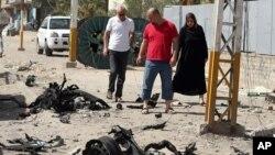 Waga melewati lokasi serangan bom mobil di Baghdad (25/6). (AP/Hadi Mizban)
