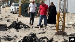 Civilians pass by the site of a car bomb attack in Baghdad's northern neighborhood of Shaab, Iraq, June 25, 2015.