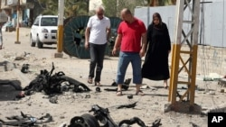 Warga melewati lokasi serangan bom mobil di Shaab, Baghdad, Irak (25/6). (AP/Hadi Mizban)