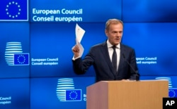 European Council President Donald Tusk holds up the Article 50 document from the UK during a media conference at the Europa building in Brussels, March 29, 2017.