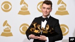"Sam Smith poses in the press room with the awards for best new artist, best pop vocal album for ""In the Lonely Hour"", song of the year for ""Stay With Me"", and record of the year for ""Stay With Me"" at the 57th annual Grammy Awards at the Staples Center on"