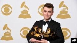 """山姆史密斯手持奖杯在格莱美奖新闻大厅亮相。他的单曲""""与你同在""""被评为最佳歌曲和年度最佳制作两个奖项。此外,史密斯还荣获年度最佳新人奖,并凭借""""孤独时刻""""夺得最佳流行演唱专辑奖。"""