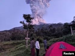Beberapa wisatawan memperhatikan Gunung Merapi yang sedang erupsi, di Cangkringan, Sleman, Yogyakarta, 3 Maret 2020. (Foto: Antara via Reuters)