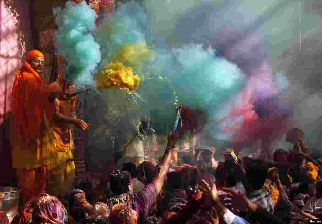Hindu priests throws colored powder at the devotees during Holi celebrations at Bankey Bihari temple in Vrindavan, in the northern Indian state of Uttar Pradesh. Holi, also known as the Festival of Colors, heralds the beginning of spring and is celebrated all over India.
