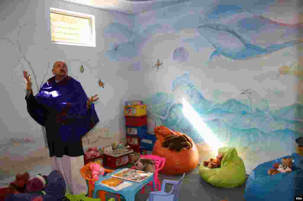 Hospice psychologist Cameron Hogg shows off murals in a pastel-filled Wits Hospice playroom. Opposing walls are filled with African elephants lumbering toward a burnt-orange sunset. (Photo by Darren Taylor)