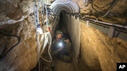 FILE - An Israeli army officer shows journalists a tunnel allegedly used by Palestinian militants for cross-border attacks from Gaza into Israel, July 25, 2014.