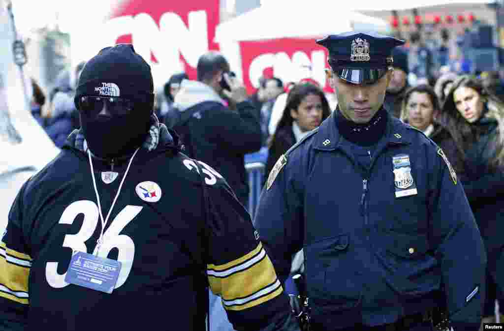 A police officer walks next to a fan at the Super Bowl Boulevard fan zone ahead of Super Bowl XLVIII in New York, Jan. 30, 2014.