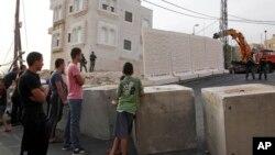 Warga Palestina mengamati tembok pemisah yang dibangun Israel untuk memisahkan permukiman warga Yahudi dan warga Muslim di Yerusalem timur, Minggu (18/10).