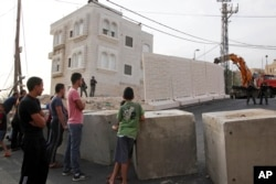 Người Palestine đứng nhìn một bức tường đang được dựng lên giữa những khu dân cư của người Palestine và người Do Thái ở Jerusalem, ngày 18 tháng 10, 2015.