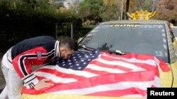 Un conducteur de taxi albanais embrasse le drapeau américain après la victoire de Trump, à Tirana, Albanie, le 10 novembre 2016.