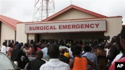 Family members and friends gather at the entrance of the Surgical and Emergency Lagos state university teaching hospital where survivals of a plane crash receive treatment in Lagos.