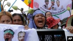Supporters shout slogans on a blocked main street near the Phnom Penh Municipality Court during their gathering to call for the release of anti-governments protesters who were arrested in a police crackdown, in Phnom Penh, file photo.