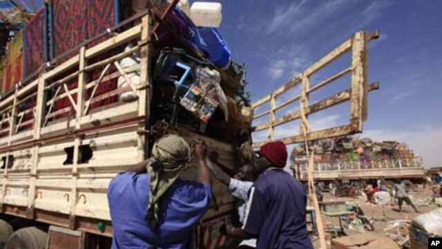 Southern Sudanese people in the north load their belongings on the truck as they prepare to leave for the south before the secession referendum, in an area called Mandela in Khartoum January 5, 2011