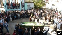 Anti-government protesters carry the coffin of Abdul Haleem Baqour during his funeral in Hula near Homs, Syria, December 10, 2011. Baqour was killed by shrapnel during shelling by the government army on Hula last week.
