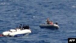 Des marins de l'USNS Trenton vont au secours des gens d'un canot en caoutchouc renversé, à gauche, dans la mer Méditerranée, le 12 juin 2018.