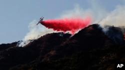 灭火飞机在加州阿祖萨一处野火现场附近向一座山坡喷洒阻燃剂。(2016年6月20日)