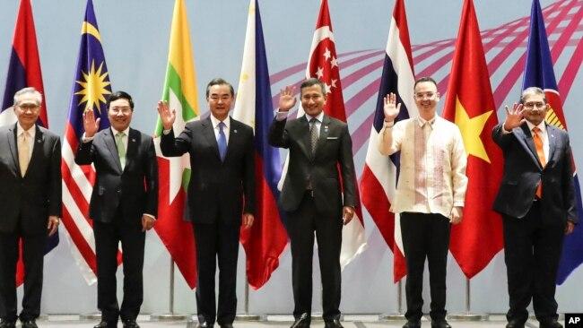Bộ trưởng Ngoại giao Việt Nam Phạm Bình Minh và ông Vương đứng gần nhau trong khi chụp ảnh chung với các nhà ngoại giao ASEAN ở Singapore.