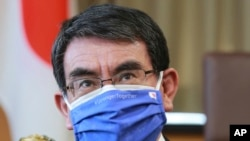 In this March 29, 2021, file photo, Japanese Vaccine Minister Taro Kono wearing a face mask with Japanese and EU flags on it speaks during an interview in Tokyo. (AP Photo/Koji Sasahara, File)
