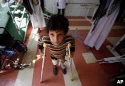 FILE - A young boy who lost his leg in the Yemen war uses a prosthetic limb at a government-run rehabilitation center in Sanaa, Yemen on March 5, 2016.