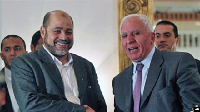 Palestinian Fatah delegation chief Azzam al-Ahmed (R) shakes hands with Hamas deputy leader Mussa Abu Marzuq after a joint press conference in Cairo on April 27, 2011 as rival Palestinian groups agreed to set up a transitional unity government and hold el