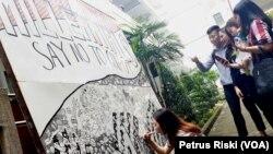 Beberapa mahasiswa memperhatikan aksi Valencia yang melukis doodle art dengan tema ajakan tidak golput pada Pemilu 2019 (foto: VOA/Petrus Riski)