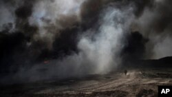 An oil worker walks next to burning oil fields in Qayara, south of Mosul, Iraq, Tuesday, Nov. 22, 2016.