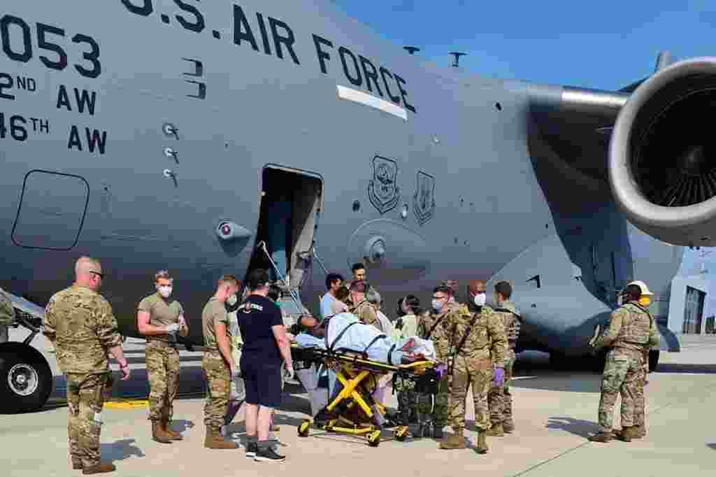 Medical support personnel from the 86th Medical Group help an Afghan mother and family off a U.S. Air Force C-17 moments after she delivered a child aboard the aircraft upon landing at Ramstein Air Base, Germany, Aug. 21, 2021. (Credit: U.S. Air Force)