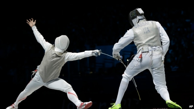 Suguru Awaji of Japan competes against  Andrea Cassara of Italy, right, in the gold medal match during the men's foil team fencing competition at the 2012 Summer Olympics.