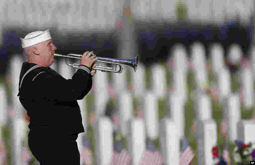 Playing a tribute to veterans, retired U.S. Navy yeoman Mark Stallins of Denver performs in Fort Logan National Cemetery, May 28, 2017, in southwest Denver, Colorado.