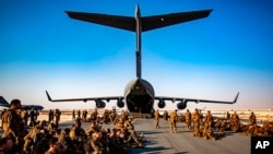 FILE - Marines assigned to the 24th Marine Expeditionary Unit await a flight to Kabul, Afghanistan, at Al Udeied Air Base, Qatar, Aug. 17, 2021.