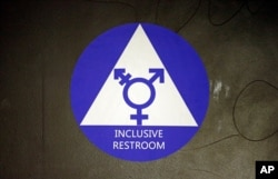 FILE - In this May 17, 2016, photo, a sticker designates a gender neutral bathroom at Nathan Hale high school in Seattle in Washington state.