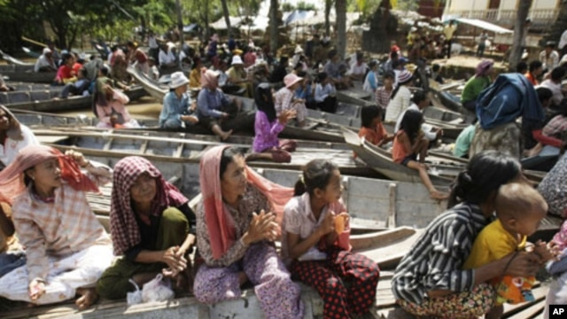 Local villagers wait on boats to receive flood donations at Prek Sussey, Kandal province, some 50 kilometers (31 miles) east of Phnom Penh, Cambodia, Tuesday, Oct. 18, 2011. More than a thousand families in a part of Kandal province Tuesday have received