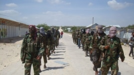Members of Somalia's al- Shabab militant group patrol on foot on the outskirts of Mogadishu, March 5, 2012.