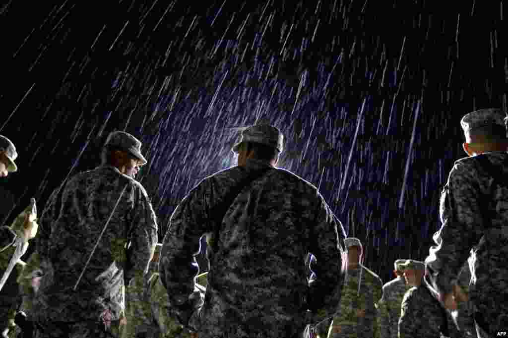 August 10: 1st Lt. Nikesh Kapadia, center, with the U.S. Army's 4th Brigade Combat Team out of Fort Campbell, Ky., stands in the rain waiting to go through customs at the Transit Center in Manas, Kyrgyzstan, on the way home after completing a deployment i