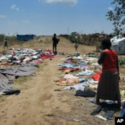 Residents of Vumilia Eldoret Camp dry out clothes after a rainstorm destroyed their tent