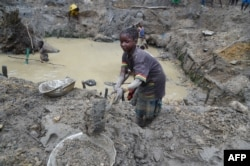 FILE - A child gold miner works in a traditional gold mine in the village of Gam, May 5, 2014.