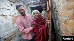 The brother, mother Ram Bai and father Mange Lal Singh (L-R) of Ram Singh, the driver of the bus in which a young woman was gang-raped and fatally injured three months ago, leave their house at Ravi Das camp in New Delhi, March 11, 2013.