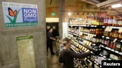 FILE - Employees stock shelves near a sign supporting non-genetically modified food at the Central Co-op in Seattle, Washington, Oct. 29, 2013.