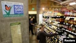 ບັນດາພະນັກງານ ວາງເຄື່ອງໃສ່ຮ້ານ ໃກ້ກັບປ້າຍ ທີ່ບອກເຖິງ ການດັດແປງທາງດ້ານພັນທຸກຳ ຫລື GMO.