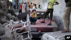 Người dân Palestine lặng nhìn cảnh hoang tàn của ngôi nhà năm thành viên gia đình Ghannam bị giết trong cuộc tấn công bằng tên lửa ở trại tỵ nạn Rafah, miền nam dải Gaza, do Israel thực hiện, 11/7/2014.