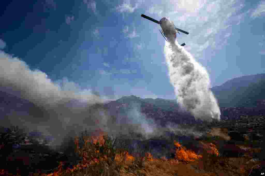 A helicopter drops water over a wildfire in Cabazon, California, August 8, 2013.