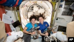 In this photo released by NASA, U.S. astronauts Jessica Meir, left, and Christina Koch pose for a photo in the International Space Station, Oct. 17, 2019.