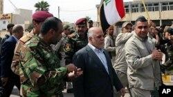 El primer ministro iraquí, Haider al-Abadi, camina por las calles de Tikrit tras recuperar la ciudad.