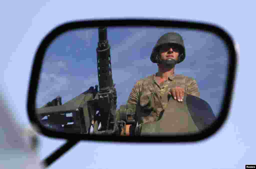A Turkish soldier is reflected on a mirror as he stands guard on top of an armoured personnel carrier on the Turkish-Syrian border, October 4, 2012.